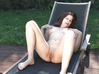 mature suntanning her pussy