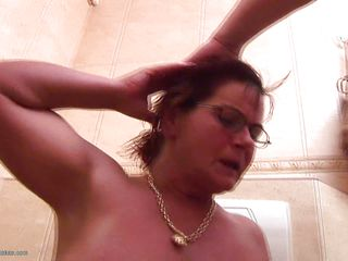 mature giving titjob and head while sitting on the toilet