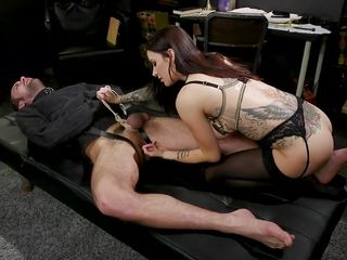 bound in a black straitjacket while the busty brunette squeezes his balls